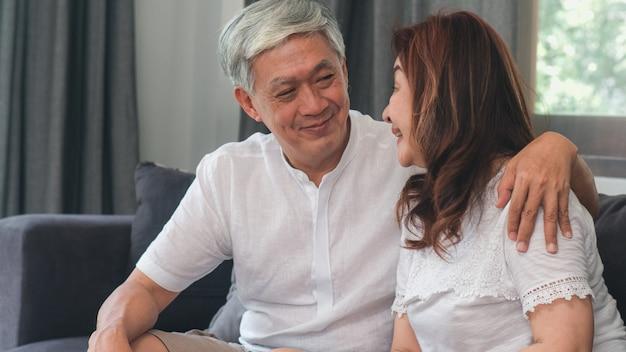 Asiatische ältere paare entspannen sich zu hause. asiatische ältere chinesische großeltern, glückliche lächelnumarmung des ehemanns und der frau, die zusammen beim auf sofa im konzept des wohnzimmers zu hause liegen spricht. Kostenlose Fotos