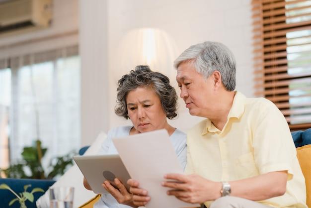 Asiatische ältere paare unter verwendung der tablette, die zu hause im wohnzimmer fernsieht, paare genießen liebesmoment beim auf sofa liegen, wenn sie zu hause entspannt werden. Kostenlose Fotos