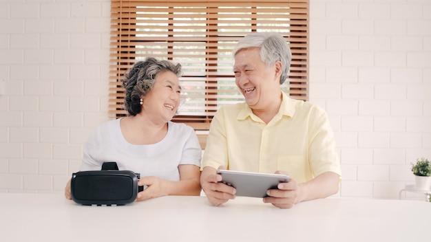 Asiatische ältere paare unter verwendung der tablette und des simulators der virtuellen realität, die spiele im wohnzimmer spielen, paare, die unter verwendung der zeit glücklich sich fühlen, die zusammen auf tabelle zu hause liegt. Kostenlose Fotos