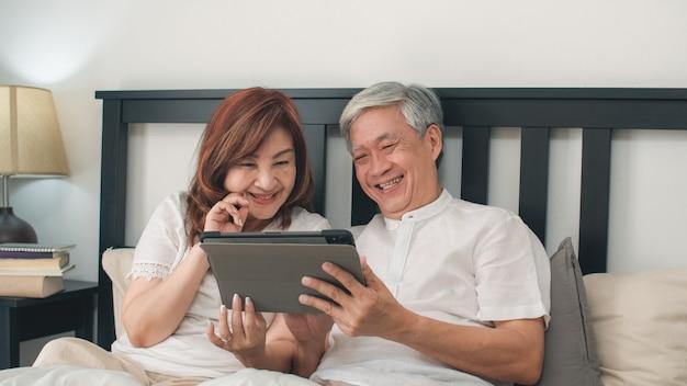 Asiatische ältere paare unter verwendung der tablette zu hause. asiatische ältere chinesische großeltern, ehemann und frau, die nach glücklich sind, wachen auf und passen film auf, auf bett im konzept des schlafzimmers zu hause morgens zu liegen. Kostenlose Fotos