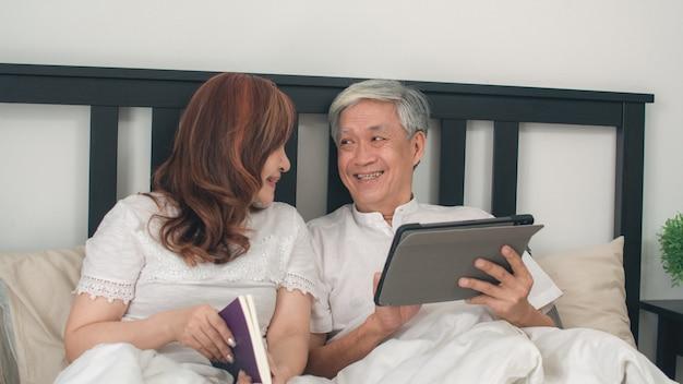 Asiatische ältere paare unter verwendung der tablette zu hause. asiatische ältere chinesische großeltern, ehemannuhrfilm und frau lasen buch, nachdem sie aufwachten und morgens auf bett im konzept des schlafzimmers zu hause lagen. Kostenlose Fotos