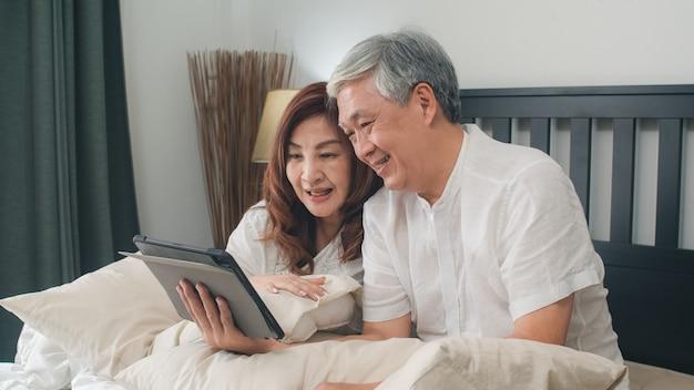 Asiatische ältere paare unter verwendung der tablette zu hause. asiatische ältere chinesische großeltern, videoanruf, der mit familienenkelkind spricht, scherzt beim auf bett im konzept des schlafzimmers zu hause morgens liegen. Kostenlose Fotos