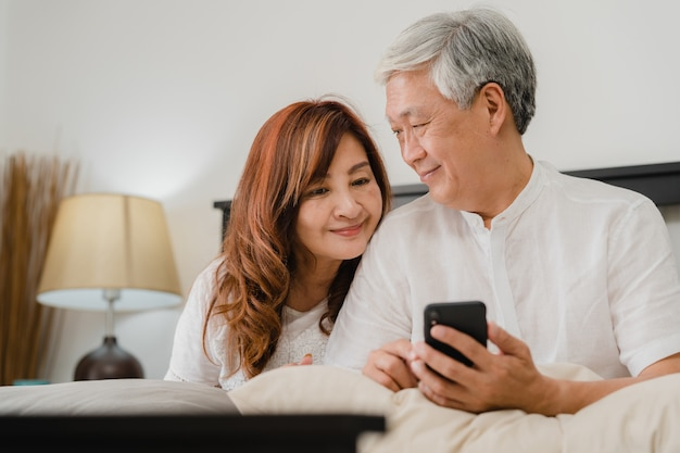 Asiatische ältere paare unter verwendung des handys zu hause. asiatische ältere chinesische großeltern, ehemann und frau, die nach glücklich sind, wachen auf und passen film auf, auf bett im konzept des schlafzimmers zu hause morgens zu liegen. Kostenlose Fotos