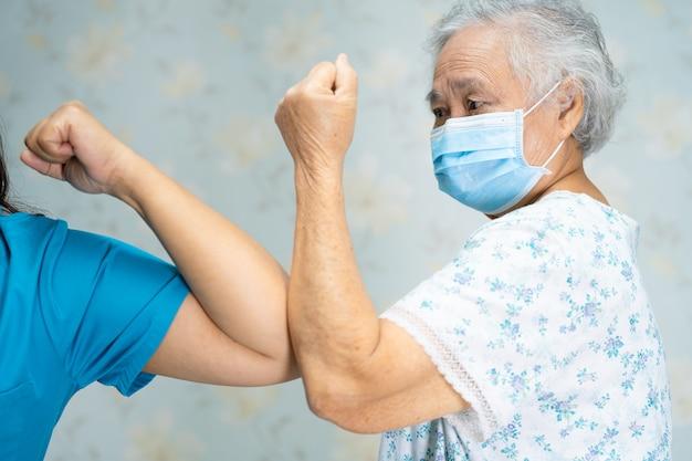 Asiatische ärzte und ältere patienten stoßen mit ellbogen an die soziale distanz, um das covid-19-coronavirus zu vermeiden. Premium Fotos