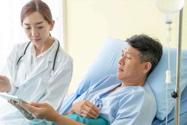 Asiatische ärztin, die auf krankenhausbett sitzt und mit älterem patienten sich bespricht Premium Fotos