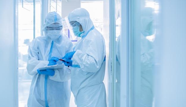 Asiatische ärztin im persönlichen schutzanzug mit maskenschrift auf quarantäne-patientendiagramm, reagenzglas mit blutprobe für das screening des coronavirus haltend. coronavirus, covid-19-konzept. Premium Fotos