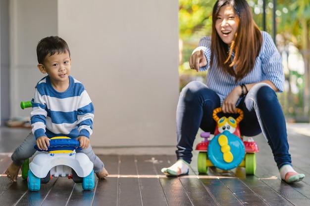 Asiatische alleinerziehende mutter mit sohn spielen mit autospielzeug zusammen, wenn sie im modernen haus leben Premium Fotos