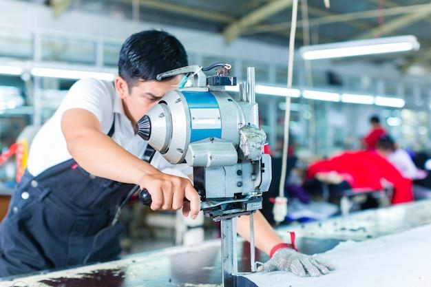 Asiatische arbeitskraft, die eine maschine in einer fabrik verwendet Premium Fotos