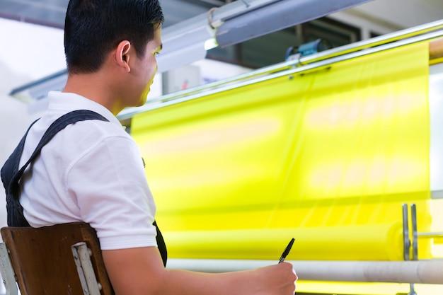 Asiatische arbeitskraft steuert gewebe in der textilfabrik Premium Fotos