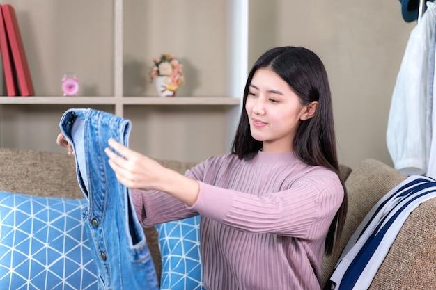 Asiatische attraktive frau, die zur neuen kleidung mit dem lächeln schaut Kostenlose Fotos