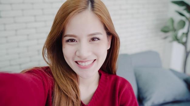 Asiatische bloggerfrau, die zu hause smartphone, der vlog video im wohnzimmer aufnimmt Kostenlose Fotos