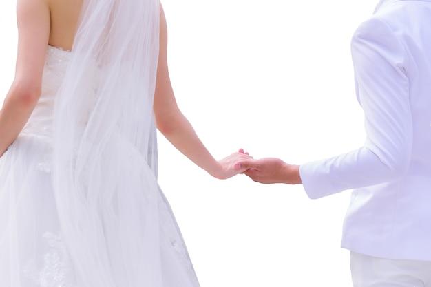 Asiatische braut im weißen hochzeitskleid und bräutigam im weißen anzug, der hände lokalisiert auf weißer wand hält Premium Fotos