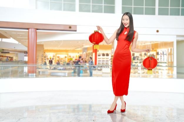 Asiatische chinesin in einem cheongsam kleid, das chinesische laterne hält Premium Fotos
