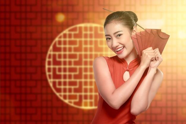 Asiatische chinesin in einem cheongsam kleid, das rote umschläge hält Premium Fotos
