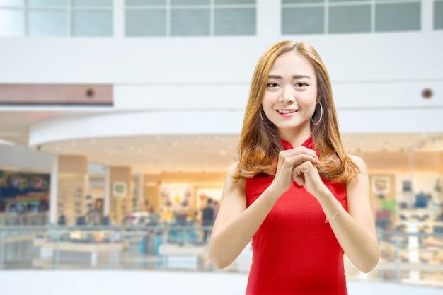 Asiatische chinesische frau in einem cheongsam kleid mit glückwunschgeste Premium Fotos