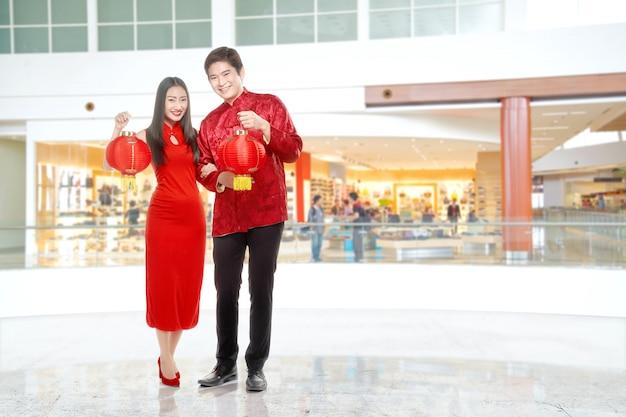 Asiatische chinesische paare im cheongsam kleid, das chinesische laterne hält Premium Fotos