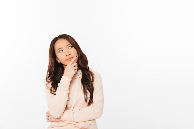 Asiatische denkende damenstellung lokalisiert Kostenlose Fotos