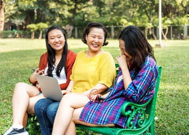 Asiatische familie benutzt digitale geräte am park Premium Fotos