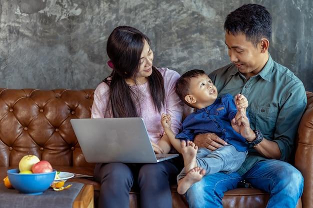 Asiatische familie mit sohn schaut die karikatur über laptop und spielt zusammen Premium Fotos