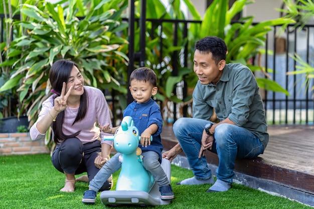 Asiatische familie mit sohn spielen mit spielzeug zusammen, wenn sie im vorderen rasen des modernen hauses leben Premium Fotos