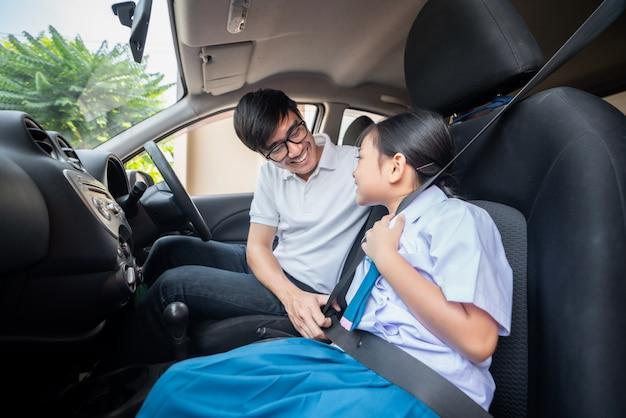 Asiatische familie mit vaterversuch zum sicherheitsgurt zu ihrer kindergartentochter, die sich vorbereitet, um zu fahren, gehen zu ihren kindern morgens zur schule. Premium Fotos