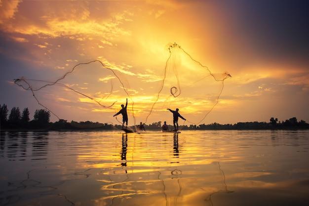 Asiatische fischer auf bootsfischen am see, thailand-landschaft Premium Fotos