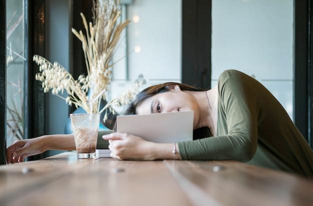 Asiatische frau der nahaufnahme lag für das lesen eines buches in der kaffeestube mit glücklichem gesicht Premium Fotos