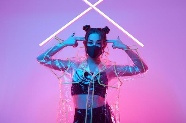 Asiatische frau der virenmaske, die gesichtsschutz um buntes neon trägt Premium Fotos