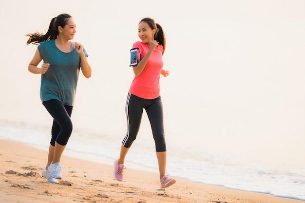 Asiatische frau des schönen jungen sports des porträts, die auf dem strand nahe meer und ozean zur sonnenaufgang- oder sonnenuntergangzeit läuft und trainiert Kostenlose Fotos