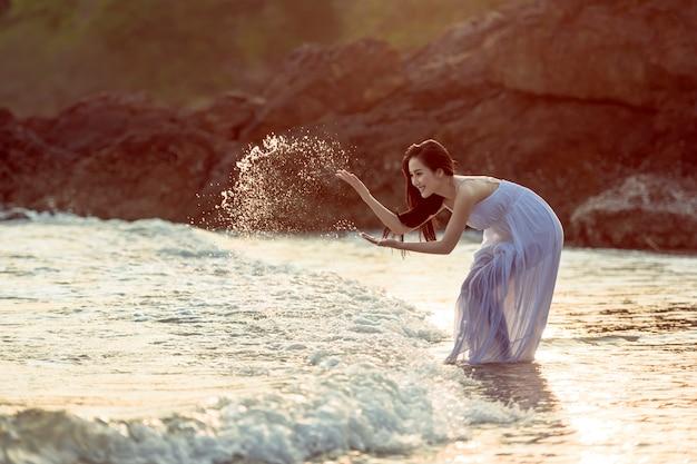 Asiatische frau, die am strand sich entspannt Premium Fotos