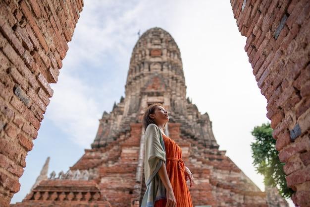 Asiatische frau, die am wat chaiwatthanaram tempel ayutthaya reist Premium Fotos