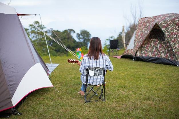 Asiatische frau, die auf picknickstuhl sitzt und gitarre spielt, während sie mit familie auf dem campingplatz in der schönen natur kampiert. Premium Fotos