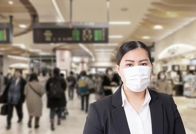 Asiatische frau, die chirurgische maske trägt, um grippe-krankheit corona-virus mit unscharfem bild von überfüllt zu verhindern Premium Fotos