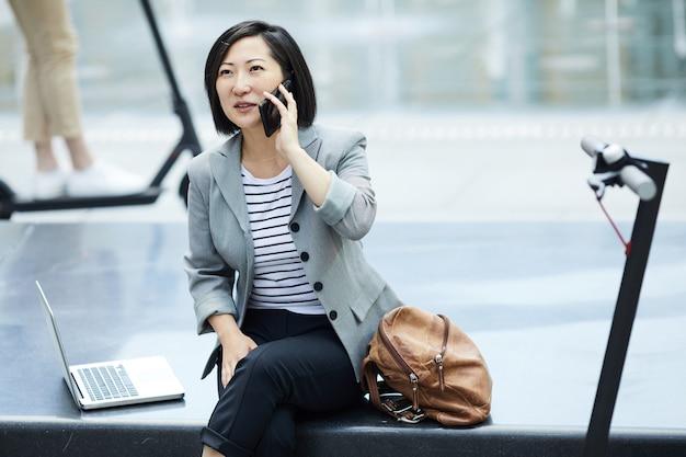 Asiatische frau, die durch smartphone in der stadt spricht Premium Fotos