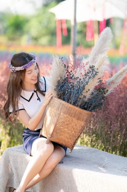 Asiatische frau, die grasblumenkorb am morgen am blumenfeld aufwirft und hält. Premium Fotos