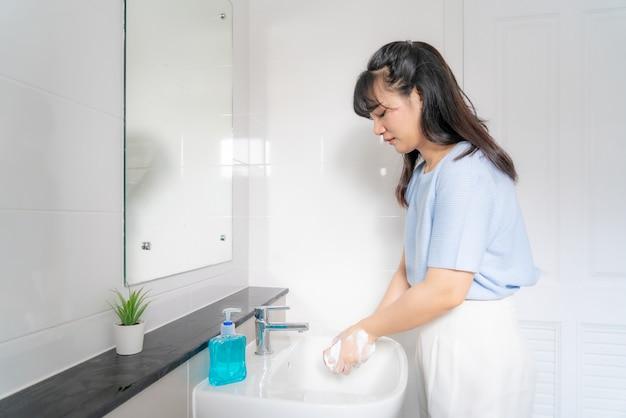 Asiatische frau, die hände mit seife unter dem wasserhahn mit wasser im badezimmer zu hause wäscht. stoppen sie den covid-19-ausbruch Premium Fotos