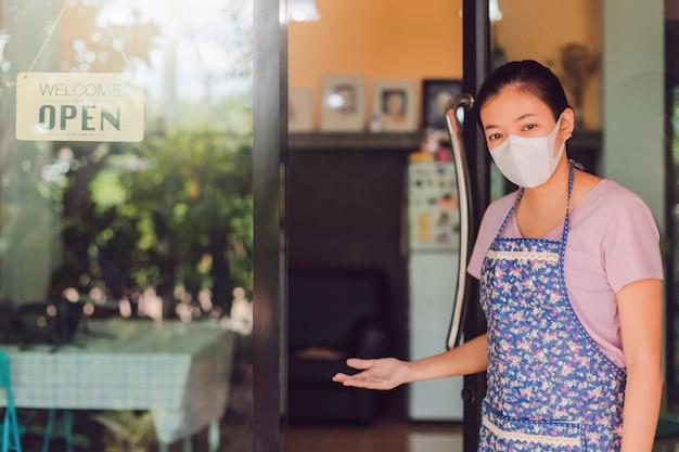 Asiatische frau, die maske steht mit offenem schild am fenster im kaffeehaus steht. Premium Fotos