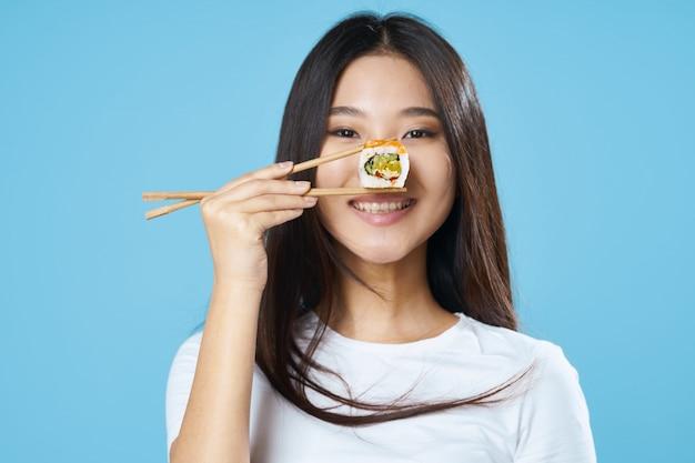 Asiatische frau, die mit lebensmittelporträt, sushi aufwirft Premium Fotos