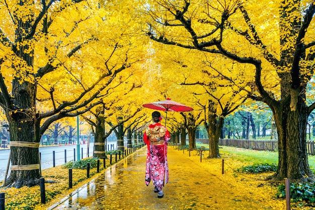 Asiatische frau, die traditionellen japanischen kimono an der reihe des gelben ginkgobaums im herbst trägt. herbstpark in tokio, japan. Kostenlose Fotos