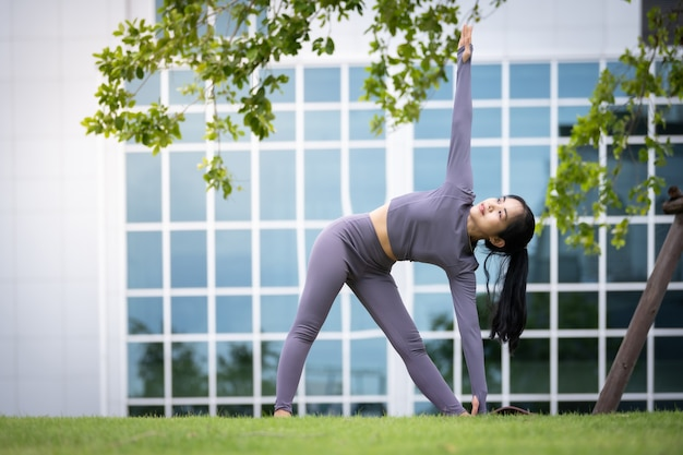 Asiatische frau, die yoga in einem städtischen garten praktiziert Premium Fotos