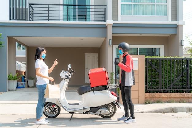 Asiatische frau holen lieferung lebensmittelbeutel von box und daumen hoch form kontaktlos oder kontakt frei von lieferung fahrer mit fahrrad vor dem haus für soziale distanzierung für infektionsrisiko. coronavirus-konzept Premium Fotos