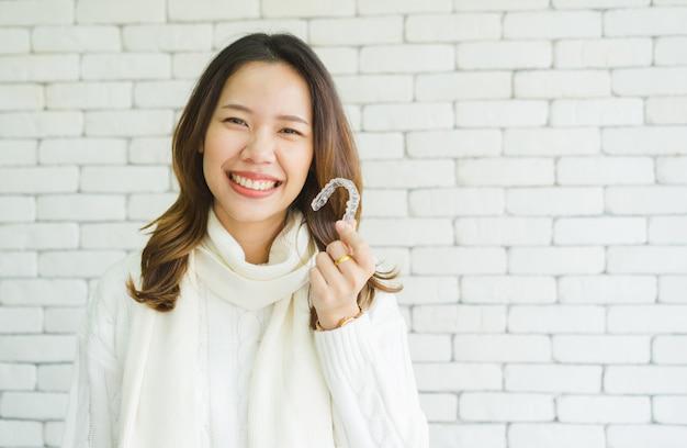 Asiatische frau lächelt mit der hand, die den halter des zahnrichters hält (unsichtbar) Premium Fotos