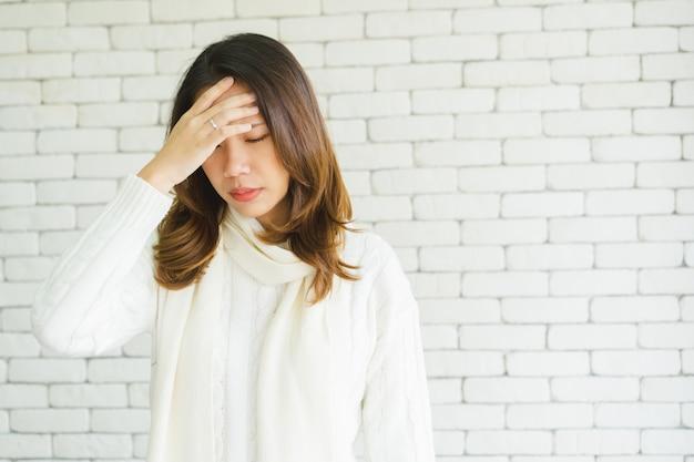 Asiatische frau mit handberührung und massage am kopf nach gefundenem migräne-symptom Premium Fotos