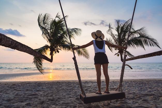 Asiatische frau sommerzeit entspannen auf schaukel im strand bei sonnenuntergang thailand sommersaison Premium Fotos