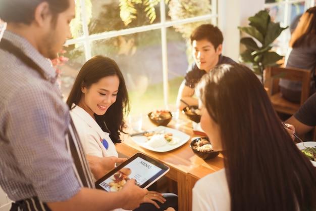Asiatische frau und ihre freunde bestellten von der speisekarte, der kellner im restaurant am morgen. Premium Fotos