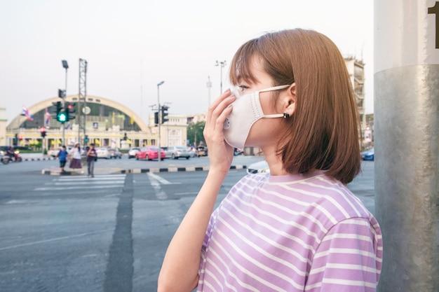 Asiatische frau, welche die n95 atemschutzmaske gegen luftverschmutzung an der straße und am verkehr in bangkok trägt Premium Fotos