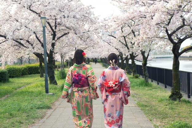 Asiatische frauen der paare, die traditionellen japanischen kimono in kirschblüte tragen, arbeiten in osaka, japan im garten. Premium Fotos