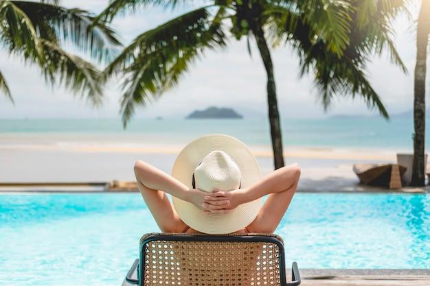 Asiatische frauen, die im schwimmbad-sommerurlaub am strand entspannen Premium Fotos