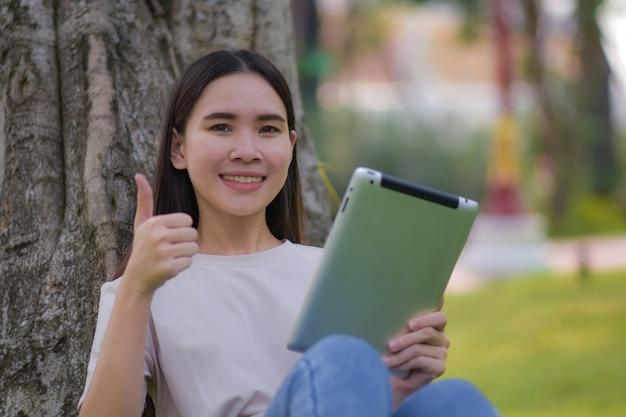 Asiatische frauen halten tablette auf sozialem netzwerk und kaufen online durch internet, das im stadtpark sitzt Premium Fotos