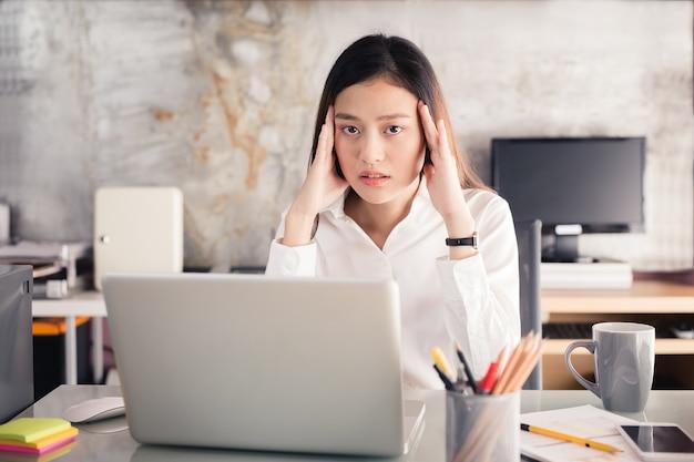 Asiatische frauen stressig mit einem notebook für eine lange zeit arbeiten, office-syndrom-konzept Premium Fotos